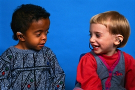 two children with hearing impairments smiling